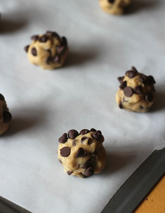 Malted chocolate chip cookie dough balls on a parchment-lined baking sheet