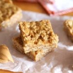 Two No Bake Peanut Butter Oat Squares, Stacked on Parchment Paper