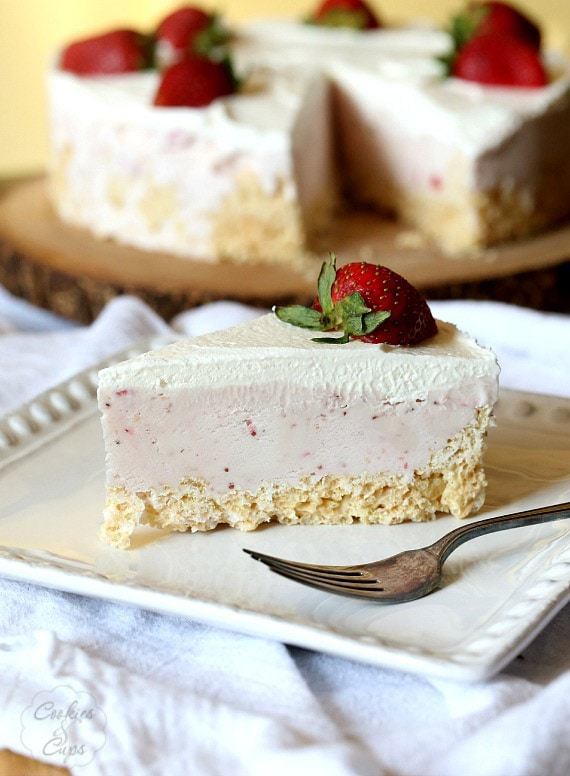 A slice of krispie treat ice cream pie with a strawberry on top on a plate
