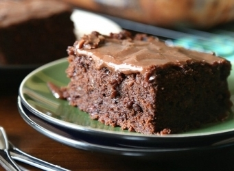 Chocolate Zucchini Cake...a rich , dense chocolate cake made with shredded zucchini. It's topped with a poured chocolate frosting that melts right into the cake!