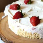 A full krispie treat ice cream pie topped with strawberries on a wooden board