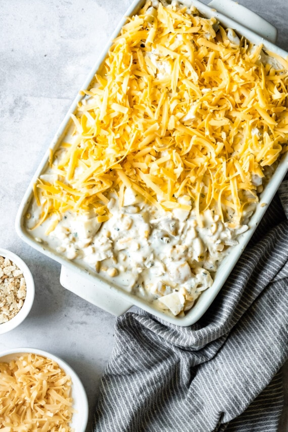 Chicken hashbrown casserole with cheese on top.