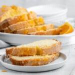 Orange pound cake slices on a plate.