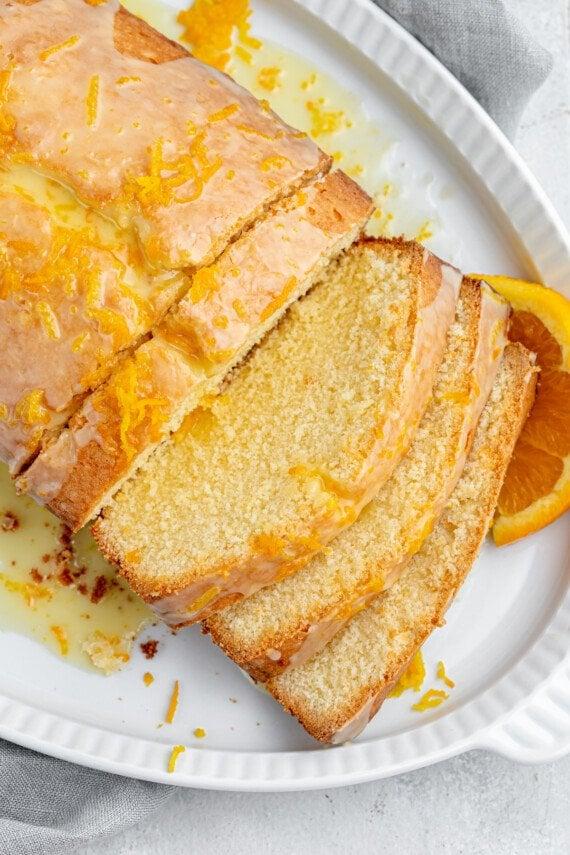 Orange glazed cake slices on a serving platter.