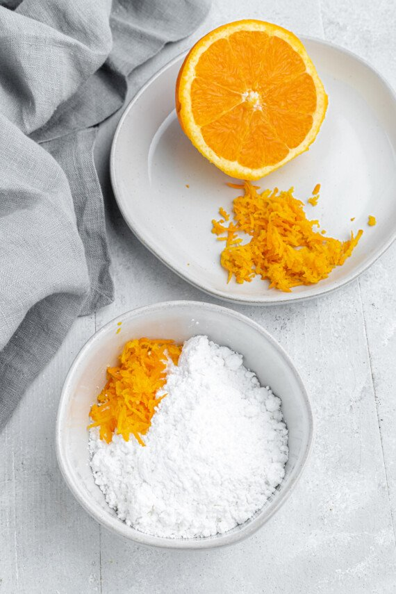 Orange zest on a plate, next to a bowl of powdered sugar.