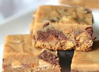 Outrageous Peanut Butter Candy Bars ~ These bars have a Nutter Butter Crust, chopped Reeses Cups, Chopped Butterfinger, peanut butter chips and chocolate chips, all topped with a creamy layer of sweetened condensed milk and peanut butter! OMG!!