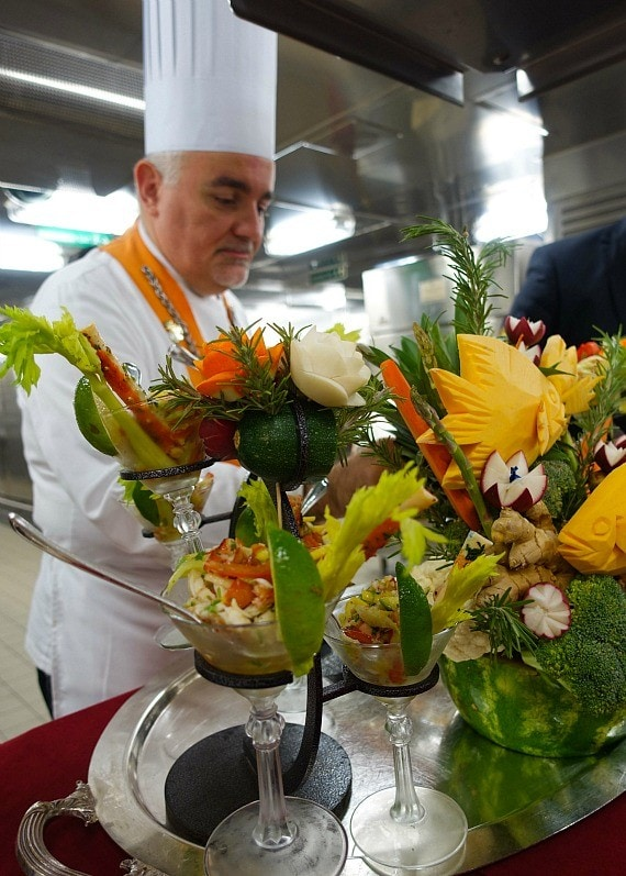 A chef with an orange sash making food disguised as floral arrangements