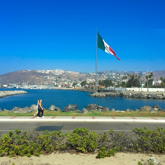 A lake in Ensenada with a large Mexican flag waving behind it and two people walking in front of it