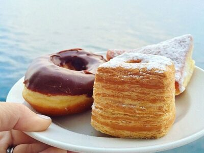 A chocolate frosted doughnut and two other pastries on a plate with ocean water in the background