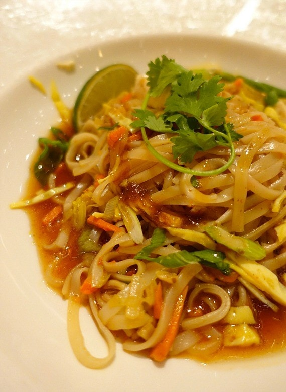 A plate of Pad Thai garnished with fresh parsley and a lime slice