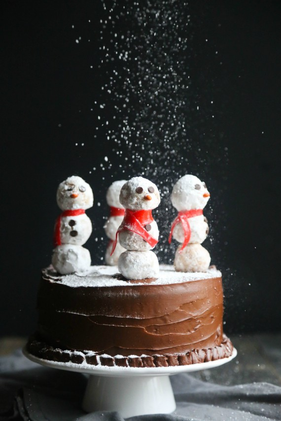 This gorgeous Snowman Cake is as simple to make as it is stunning! Donut Holes create adorable snowmen on sticks simply placed in the top of a chocolate cake!