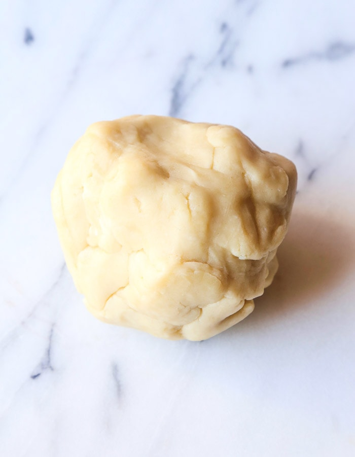 A Ball of Cream Cheese Pie Crust Dough on a Marble Surface
