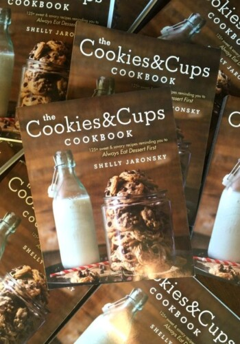A Pile of Cookies & Cups Cookbooks on a Wooden Table