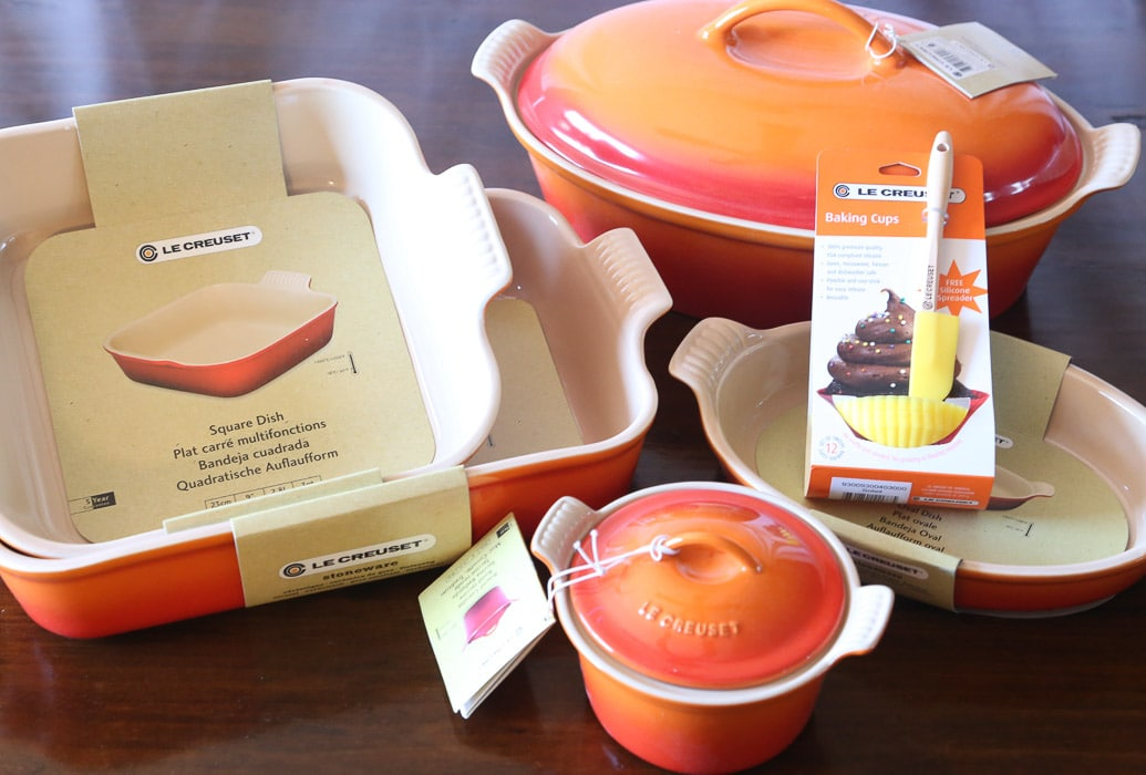 An Orange and Red Le Creuset Baking Set Arranged on a Wooden Table