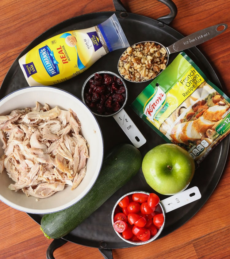 Shredded chicken, an apple, a zucchini, craisins and the rest of the salad ingredients on a black serving platter
