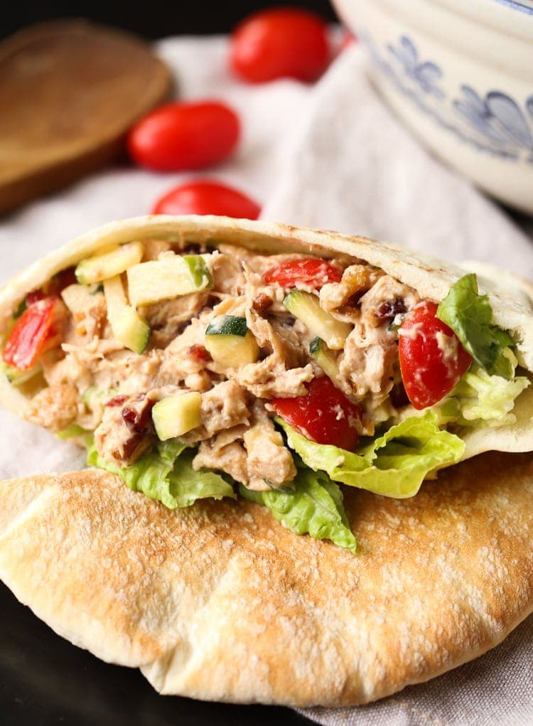 A crunchy chicken salad inside of a piece of pita bread on a table with cherry tomatoes