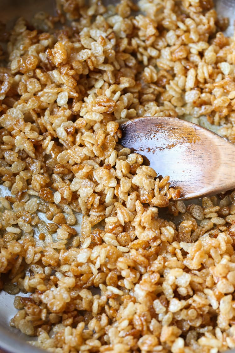 Caramelized Rice Krispies Being Stirred Around with a Wooden Spoon
