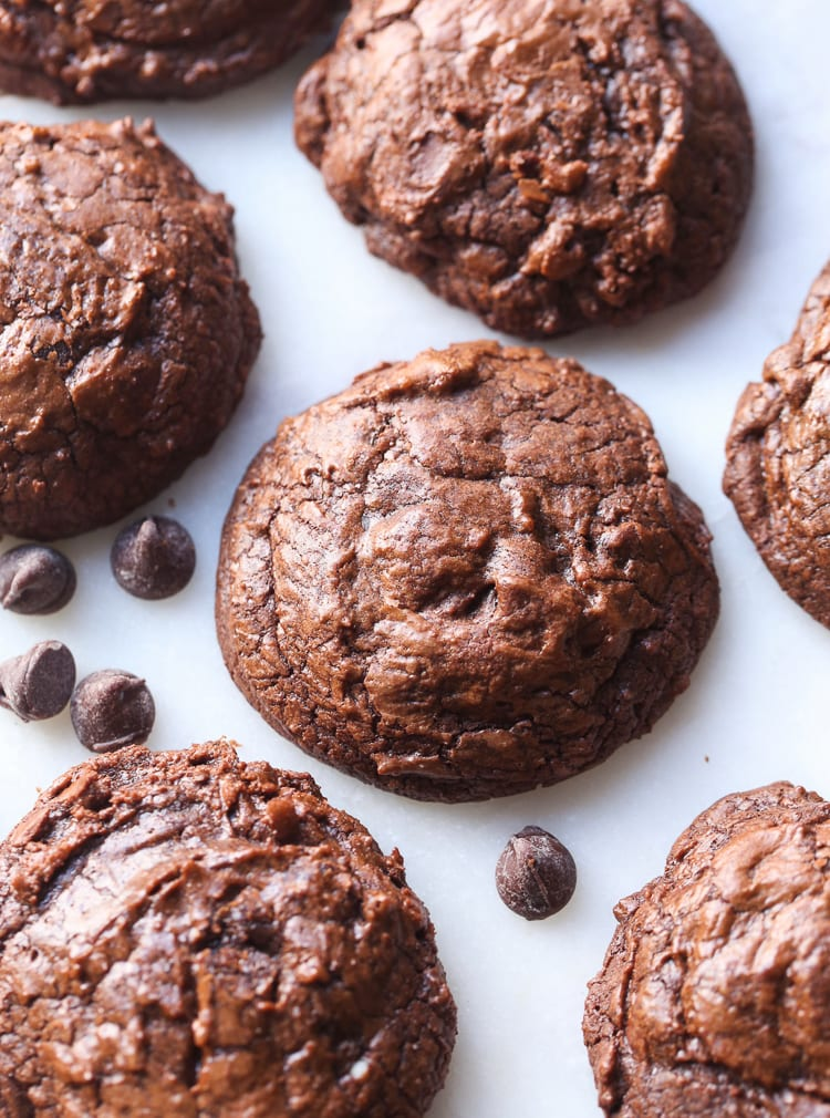 Seven Double Chocolate Cookies Arranged on a White Surface with Some Loose Chocolate Chips
