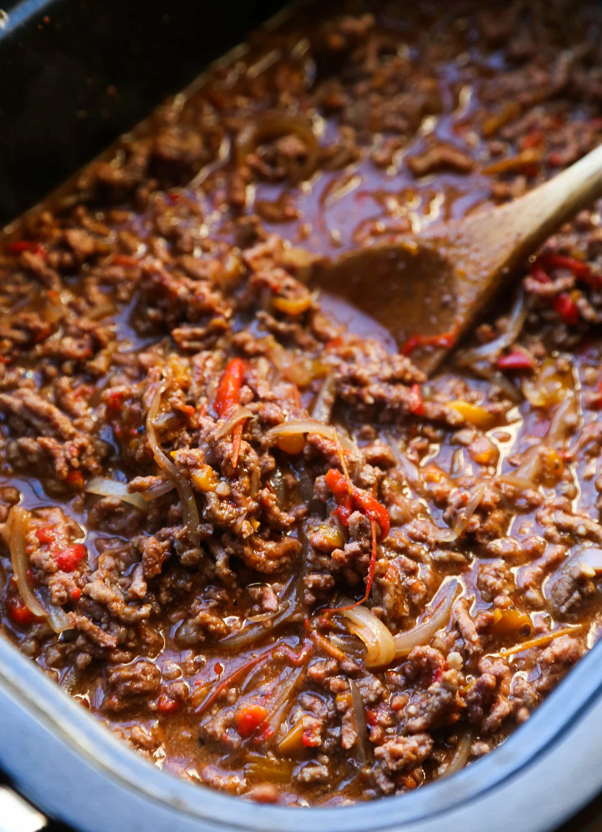 The ground beef sloppy joes mixture being mixed with a wooden spoon in a crock pot