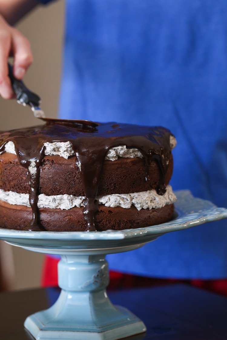 Chocolate Ganache Being Spread Over a Chocolate Cake Layered with Oreo Frosting
