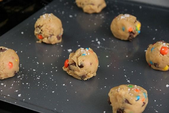 Cookie dough balls with candy pieces on a cookie sheet