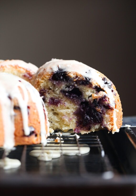 slicing a bundt cake with blueberries