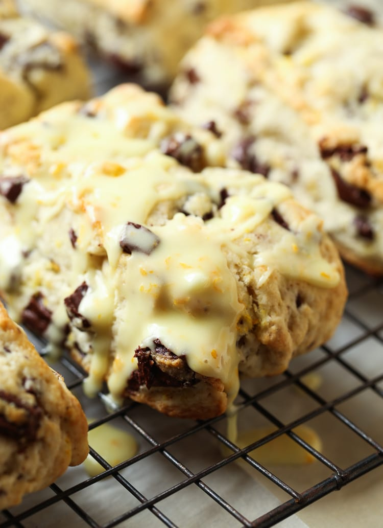 An Orange Chocolate Chunk Scone Dripping with Orange Glaze on a Cooling Rack