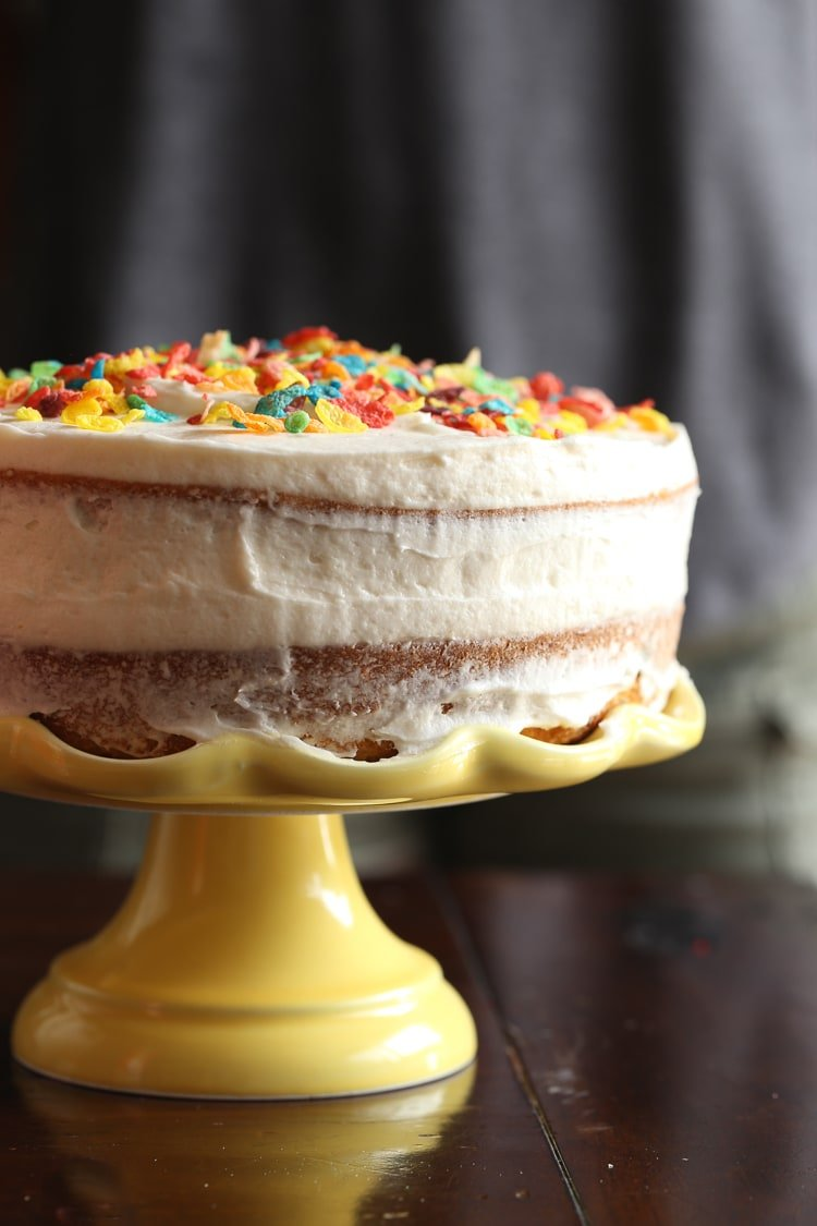 Image of a cake with cereal milk frosting and fruity pebbles on top
