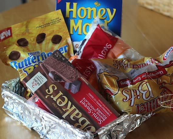 Packages of ingredients for Butterfinger Caramel Bars, including Butterfinger bits, graham crackers, marshmallows and chocolate