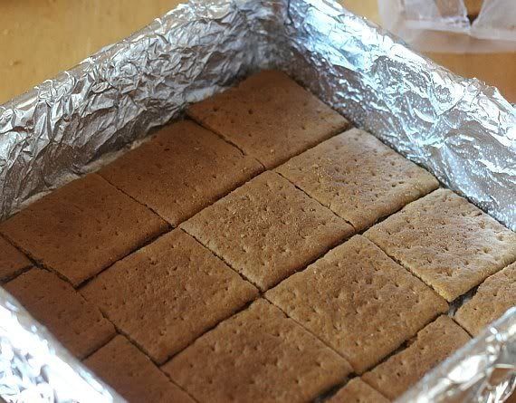 A layer of graham crackers in a foil-lined baking dish