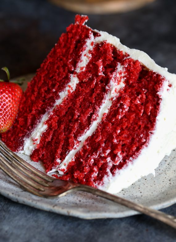 a slice of three layer red velvet cake with frosting
