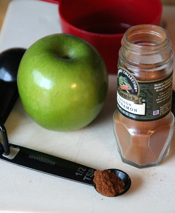 Granny smith apple and a jar of ground cinnamon