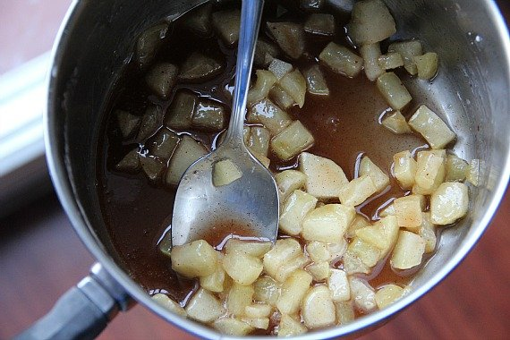 Top view of peeled, diced apples cooking with cinnamon in a saucepan