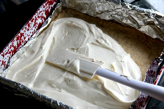 Cheesecake batter being spread over a baked crust in a foil-lined baking pan