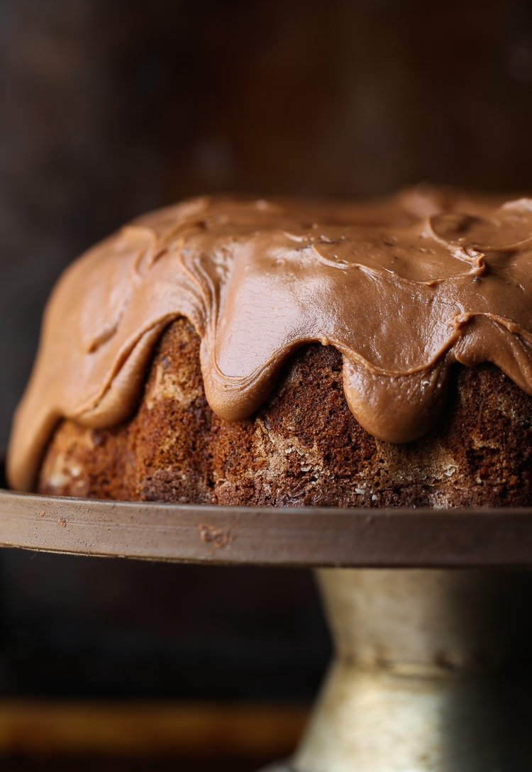 A frosted chocolate bundt cake on a metal cake stand