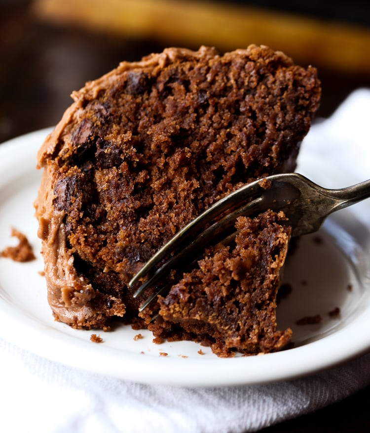 A slice of chocolate cake on a plate with a fork taking a piece out