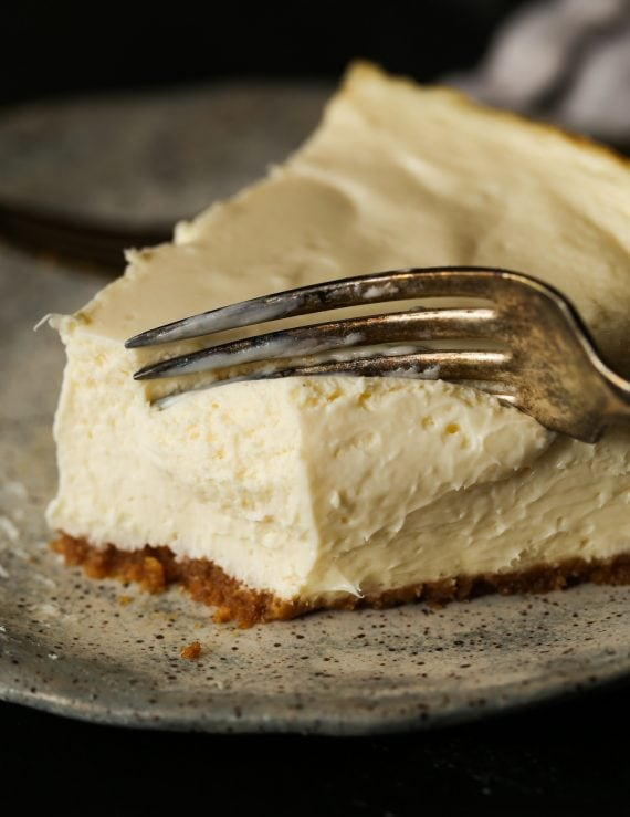 Close up of a fork cutting into a slice of cheesecake.
