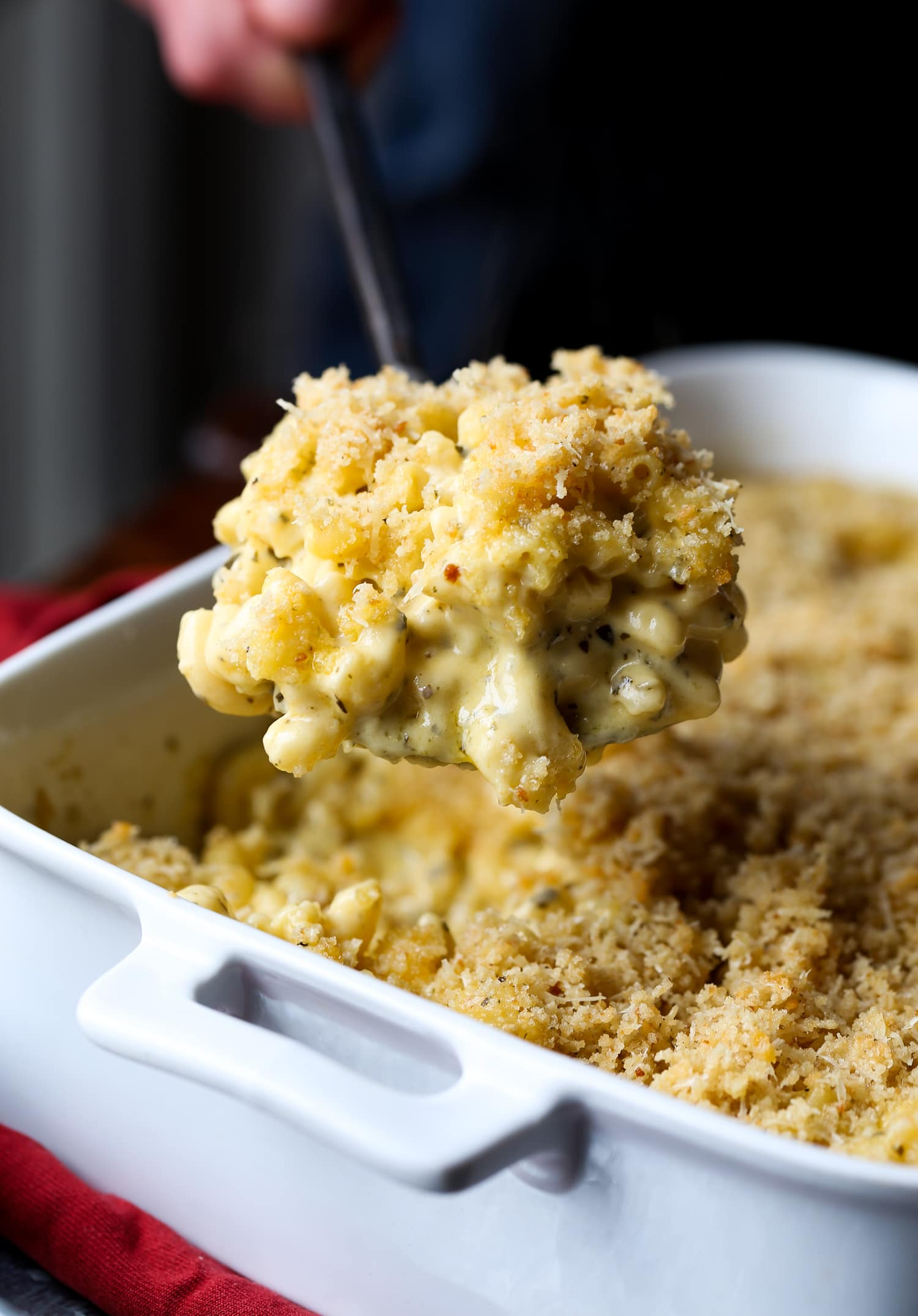 A spoon scooping mac and cheese pesto pasta out of a casserole dish