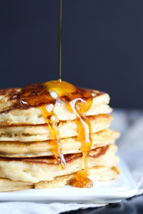 A stack of pancakes with syrup and butter