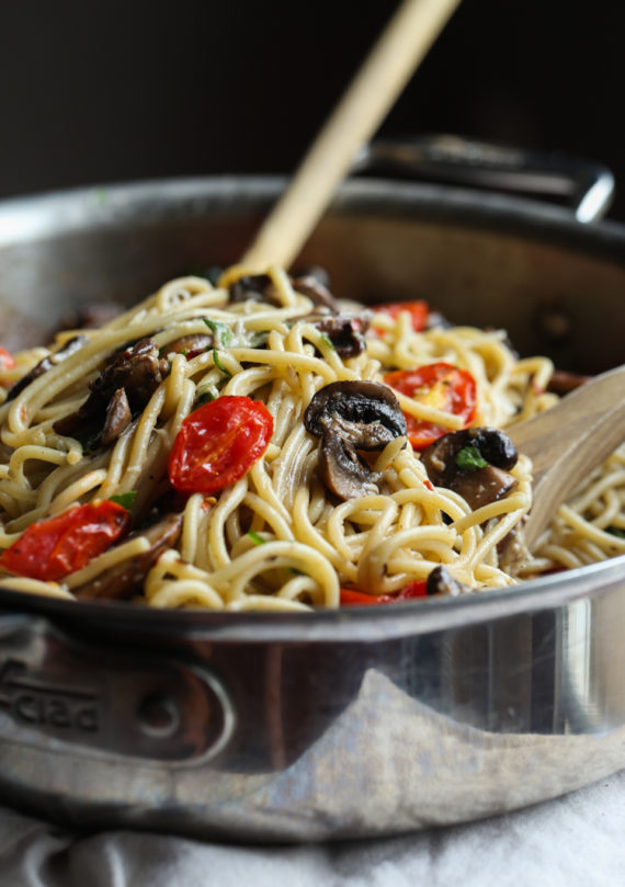 Pasta with garlic butter and roasted tomatoes and mushrooms in a stainless steel skillet