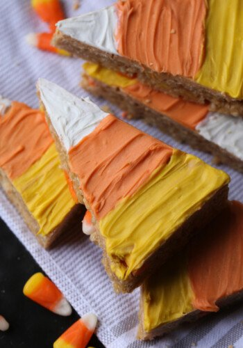 Candy Corn Scotcheroos in the shape of candy corn and decorated with white, orange, and yellow chocolate candy melts.