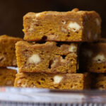 Image of 3 stacked pumpkin blondies with white chocolate chips