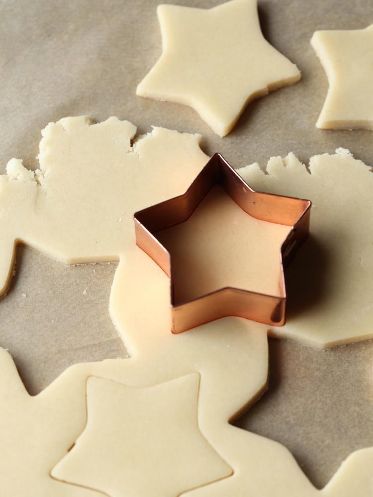 Close up of sugar cookie dough cut into stars.
