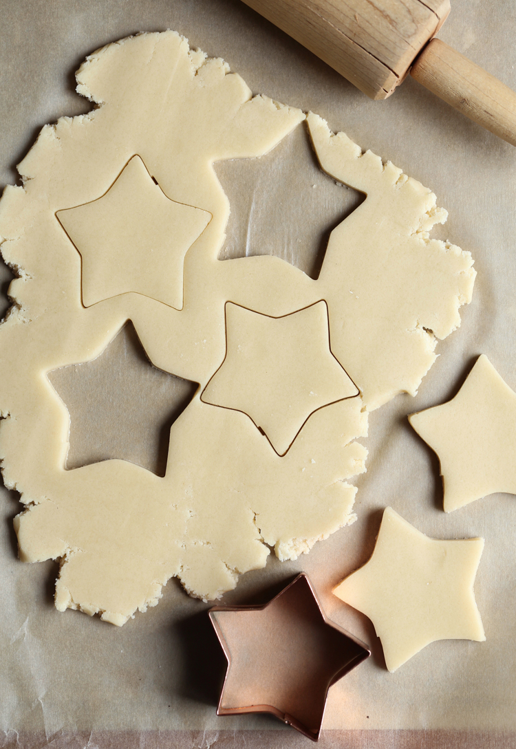 Rolled out sugar cookie dough with star shape cut outs.