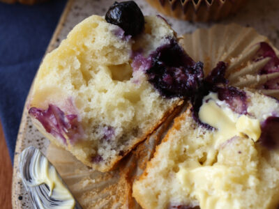 Fluffy blueberry muffins broken in half and buttered