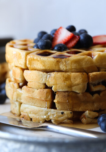 This Buttermilk waffles recipe is topped with berries and coated in maple syrup
