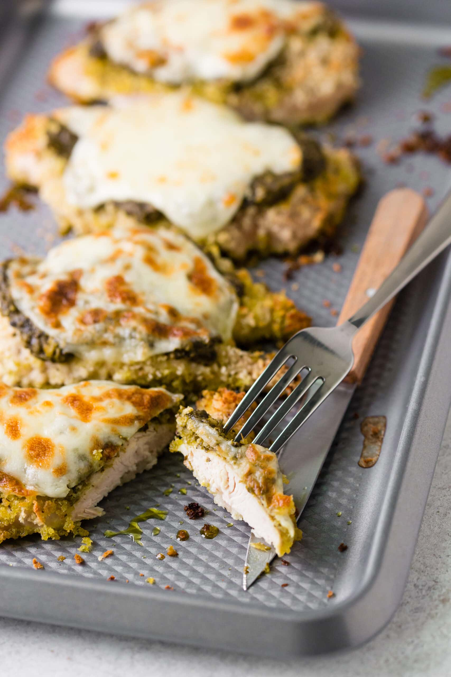 Baked Chicken topped with cheese and pesto cut on a tray