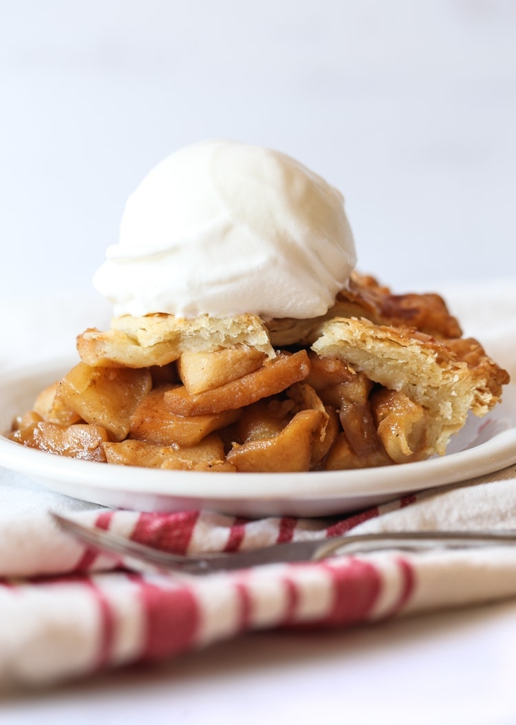 Apple pie slice topped with ice cream on a plate.