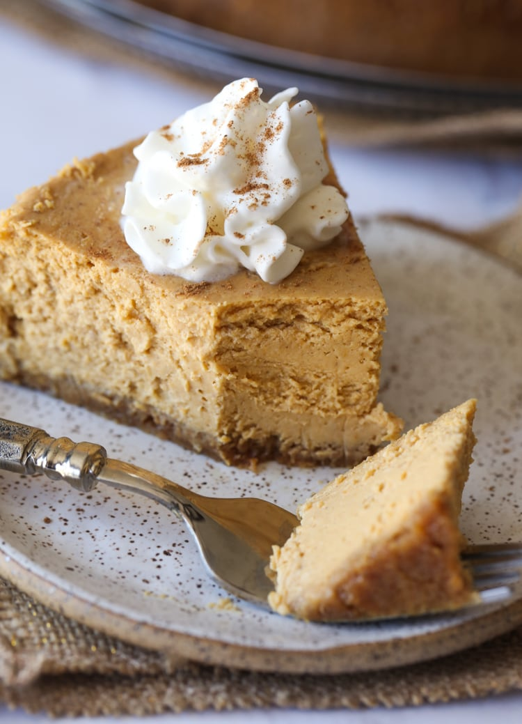 Pumpkin Pie Cheesecake with a bite taken out on a plate with whipped cream.