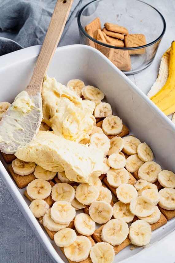 Vanilla pudding being spread on top of banana slices.